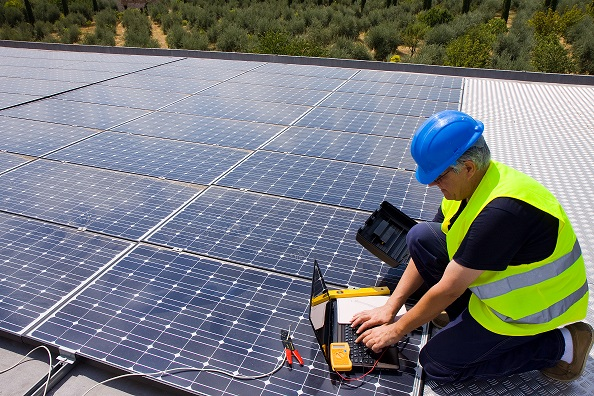 Man in high-vis vest installing solar panels on a roof