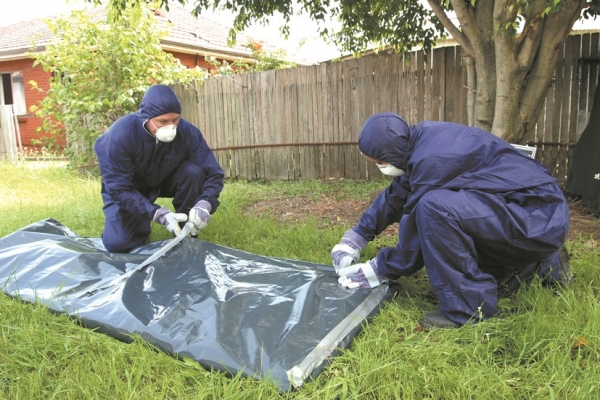Qualified asbestos removalists wrap asbestos sheeting wearing protective gear.
