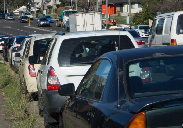 Cars parked and travelling along Western Sydney road.