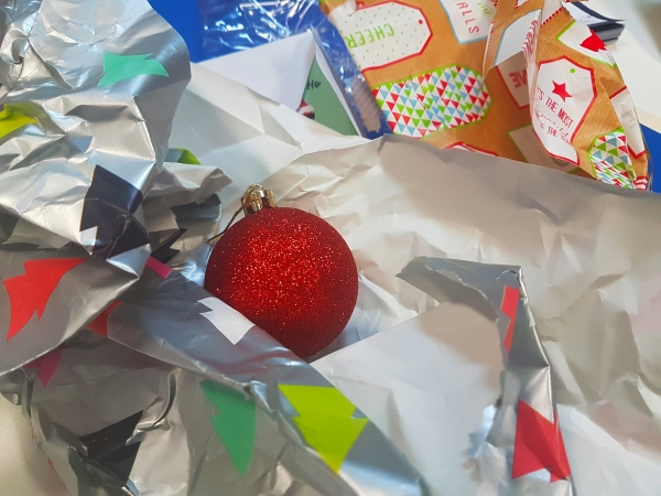 Post Christmas waste: wrapping paper and red bauble.