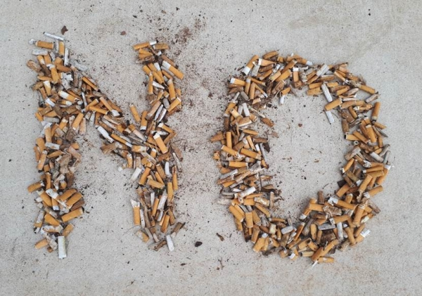 Cigarette butts, aligned to form the word 'NO'